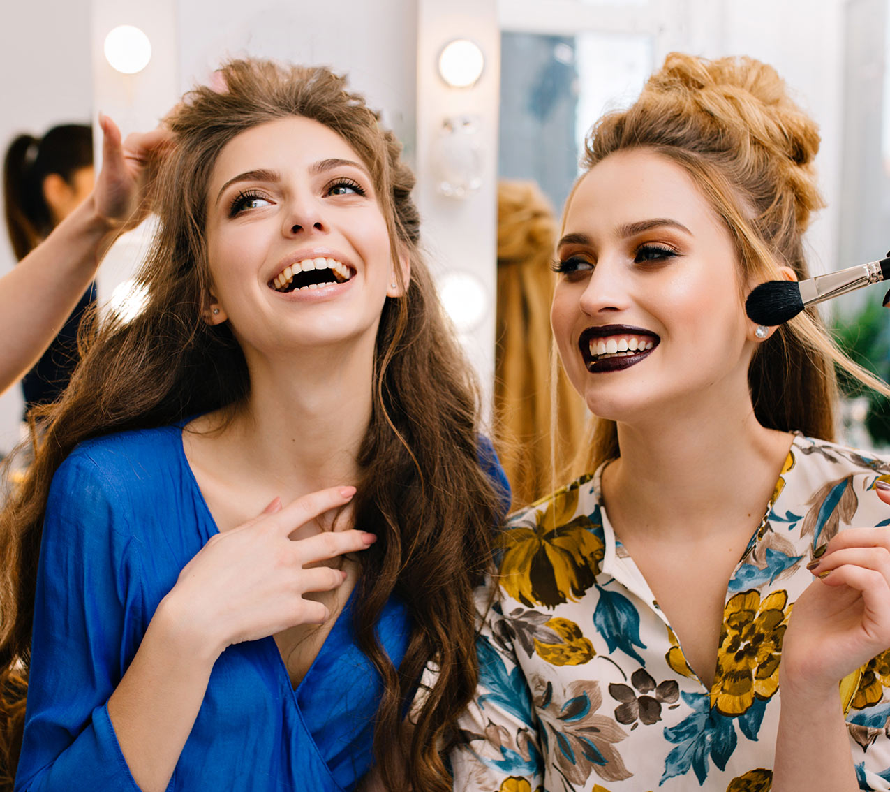 two women having hair and make up done, laughing