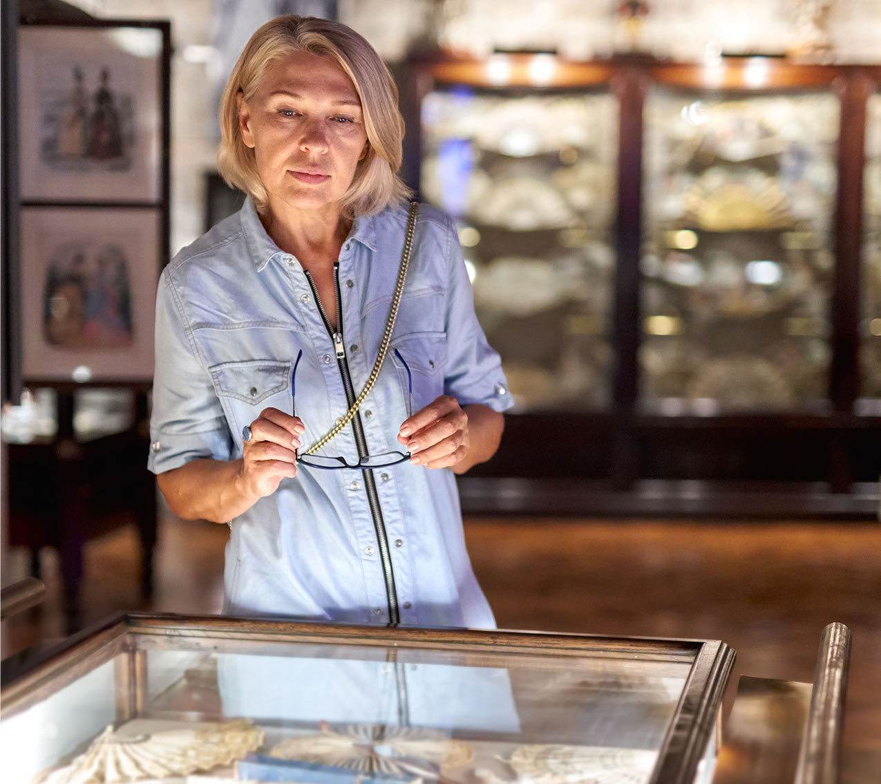 blonde haired lady with blue shirt on holding glasses and looking down into glass cabinet containing artefacts