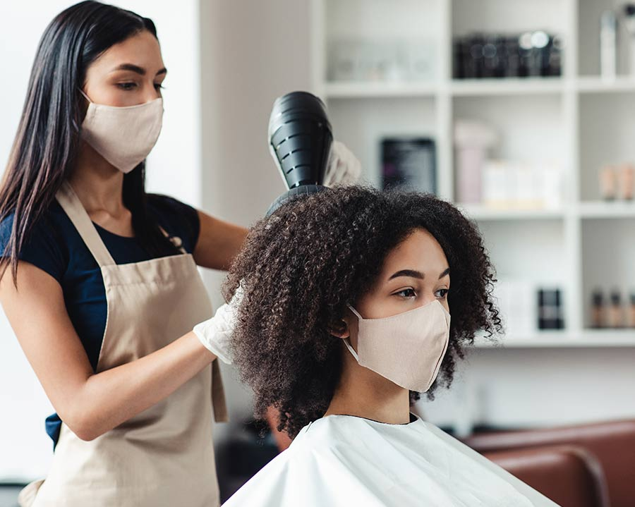 Lady having her hair styled in a hairdressers while wearing a mask